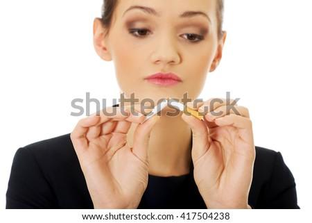 Businesswoman breaking cigarette. - stock photo