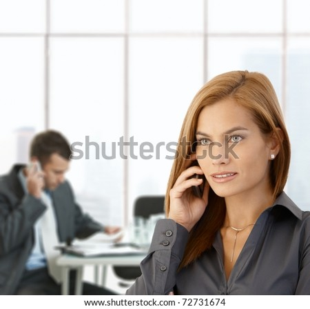 Businesswoman busy taking phone call in office, coworker working at meeting table.?