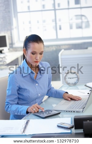 Businesswoman busy working at desk with calculator, doing financial task. - stock photo