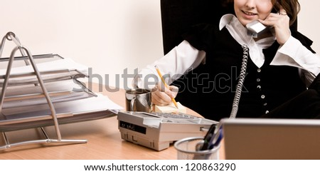 Businesswoman calling by phone and writting a note - stock photo