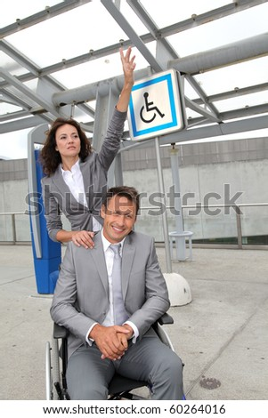 Businesswoman calling out a taxi for man in wheelchair - stock photo