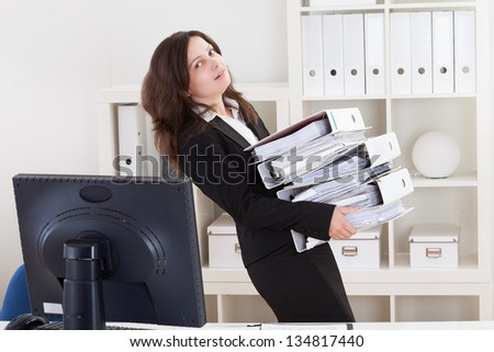 Businesswoman Carrying Stack Of Folders In Office - stock photo