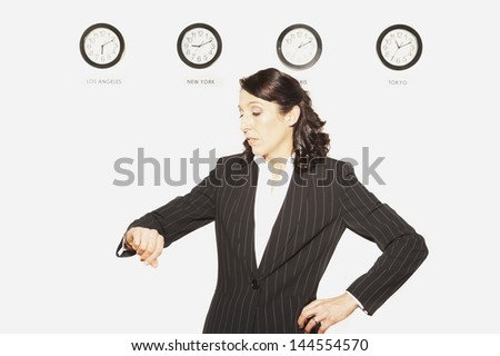 Businesswoman checking her watch in front of clocks with different time zones - stock photo