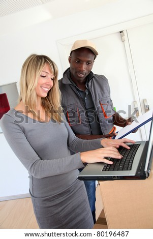 Businesswoman checking order with delivery man - stock photo