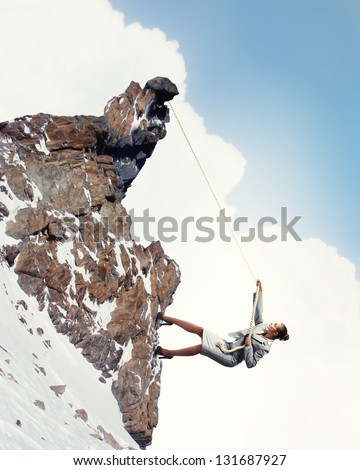 businesswoman climbing snowy steep mountain hanging on rope