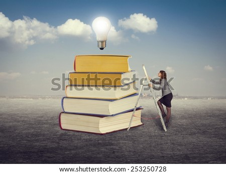 Businesswoman climbing the stairs to the foot of books for new ideas.