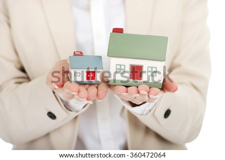 Businesswoman compares two house models. - stock photo
