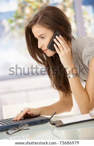 Businesswoman concentrating on work, using computer and cellphone in office.? - stock photo