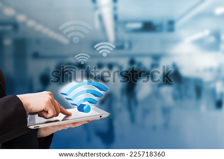 Businesswoman connecting to Wifi - stock photo