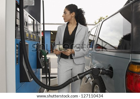 Businesswoman counting money while looking on the meter of petrol pump - stock photo
