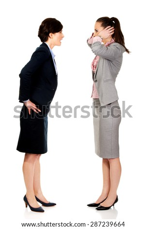 Businesswoman covering ears from her angry partner. - stock photo