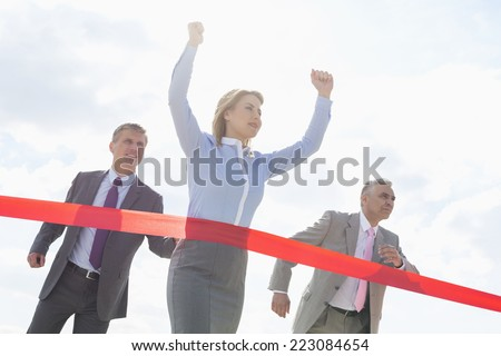 Businesswoman crossing finishing line with colleagues in background - stock photo