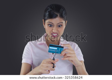 Businesswoman cutting credit card with scissors - stock photo