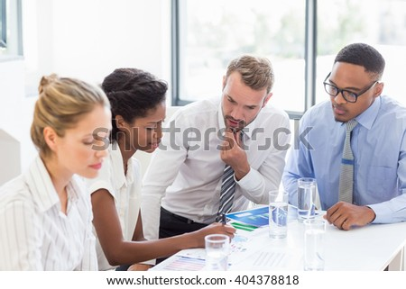 Businesswoman day dreaming in office while colleague discussing in background - stock photo