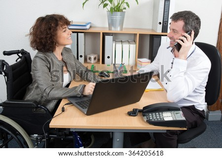 Businesswoman disabled interviewing candidat at desk in office - stock photo