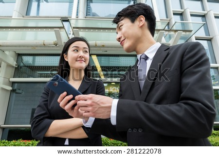 Businesswoman discuss something with businessman on cellphone - stock photo