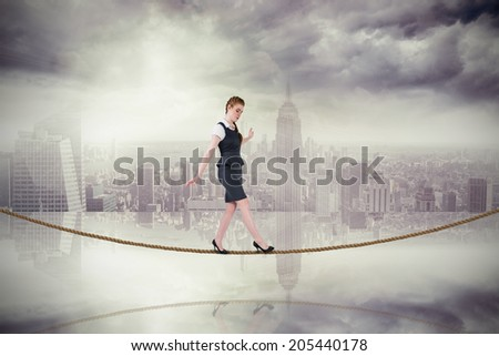 Businesswoman doing a balancing act on tightrope against room with large window looking on city - stock photo