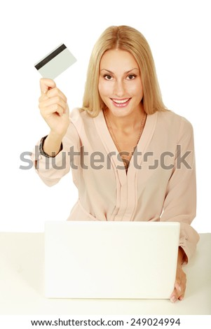 Businesswoman doing online shopping through laptop and credit card, on white background - stock photo