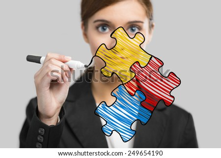 Businesswoman drawing a puzzle on a glass board - stock photo