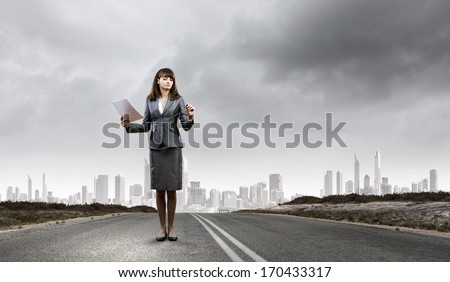 Businesswoman drawing business plan standing on road