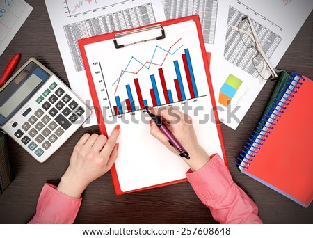 businesswoman drawing forex chart on clipboard - stock photo