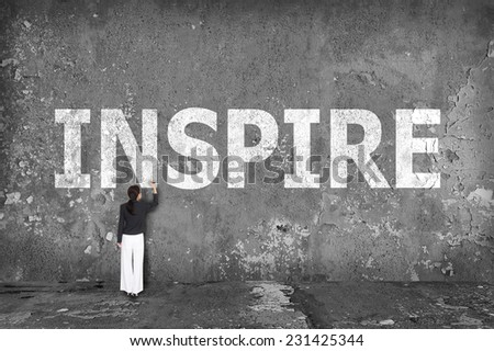 businesswoman drawing inspire on the wall
