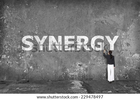 businesswoman drawing synergy on the wall