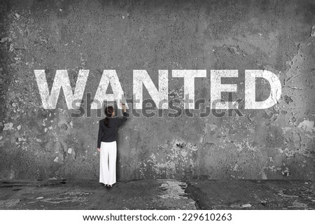 businesswoman drawing wanted on the wall