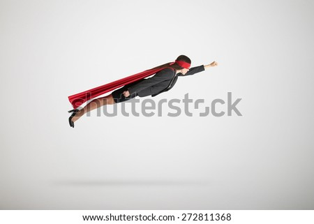 businesswoman dressed as a superhero in red mask and cloak flying over light grey background - stock photo