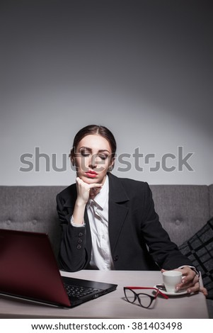 businesswoman dressed in suit and with laptop has coffee break; business lady working with portable computer;