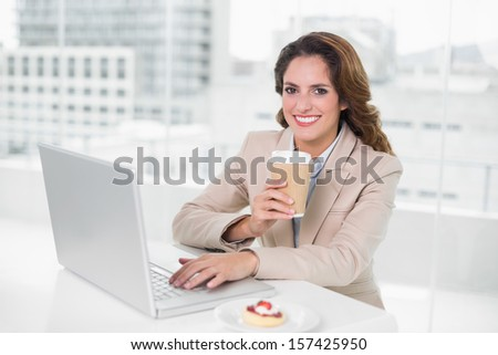 Businesswoman drinking coffee at her desk using laptop smiling at camera in bright office