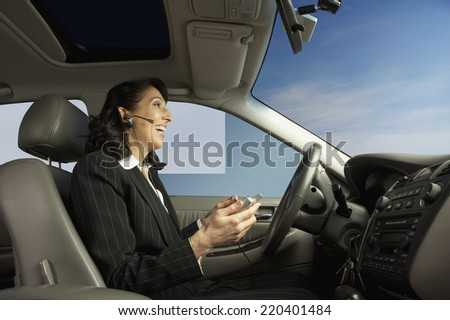 Businesswoman driving and talking on a headset - stock photo