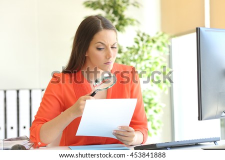Businesswoman examining a contract meticulously with a magnifying glass at office - stock photo