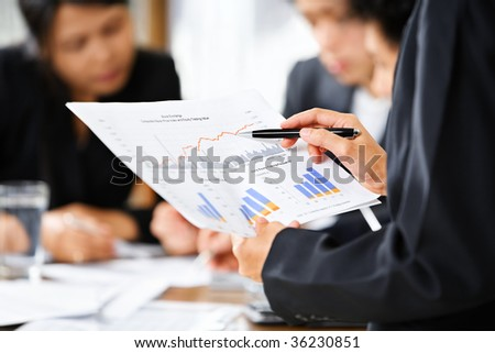Businesswoman examining graphs with other working people on background - stock photo