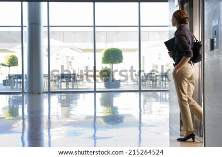 Businesswoman exiting elevator into lobby, carrying shoulder bag and folder, side view - stock photo
