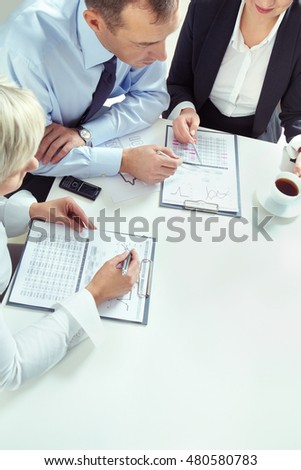 Businesswoman explaining a financial plan to colleagues at meeting