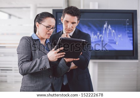 Businesswoman explaining future business plans to colleague using tablet computer - stock photo