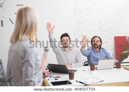 Businesswoman explaining graph on whiteboard in office while businessmen raising hands for asking questions. - stock photo