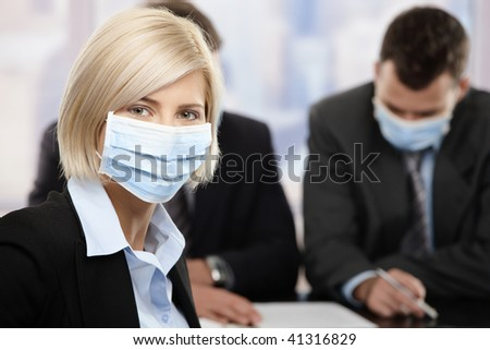 Businesswoman fearing h1n1 swine flu virus wearing protective face mask during meeting at office. - stock photo