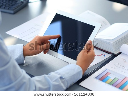 Businesswoman finger pointing to the screen of a tablet-pc - stock photo