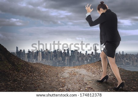 Businesswoman gesturing against large city on the horizon