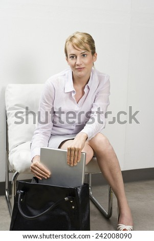 Businesswoman Getting Laptop from Purse - stock photo