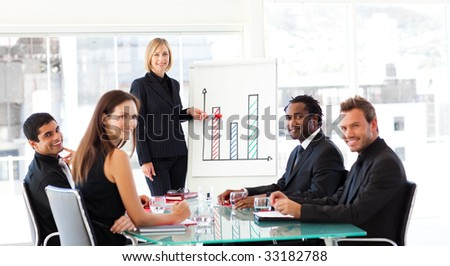 Businesswoman giving a presentation to her team and smiling at the camera
