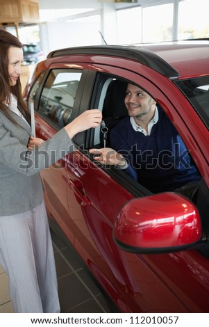 Businesswoman giving car keys to a customer in a garage