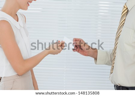 Businesswoman giving her business card to colleague in bright office - stock photo