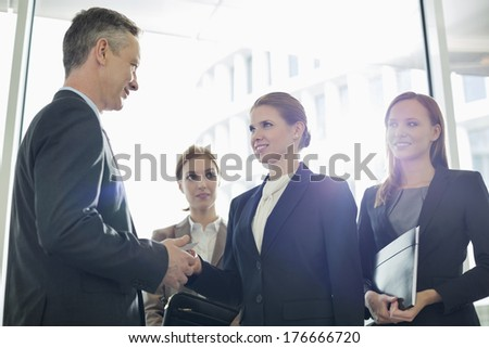 Businesswoman giving her card to businessman in office - stock photo