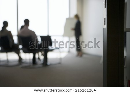 Businesswoman giving presentation to colleagues in conference room, focus on doorway in foreground - stock photo