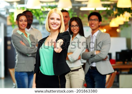 Businesswoman giving thumb up to camera in front of colleagues - stock photo