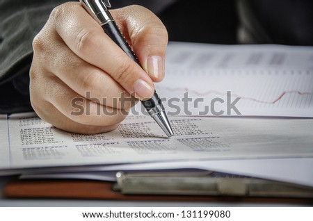 Businesswoman hand holding a pen - stock photo