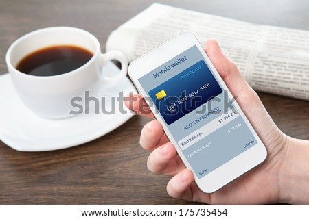 businesswoman hand holding a phone with mobile wallet onlain shopping on the screen in the office - stock photo